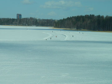 Skaters on a wide swath of ice
