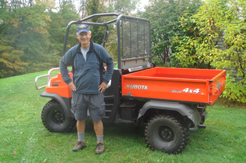 Orange and black Kubota RTV900 with Tom standing in front of it, smiling