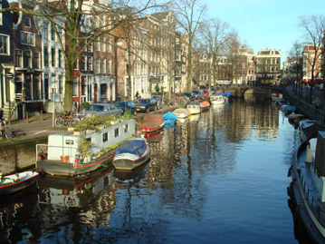 Amsterdam canal with boats moored in front of a row of houses